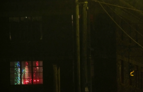 Image darkened building of streetlight with cheery lights glowing in the apartment window